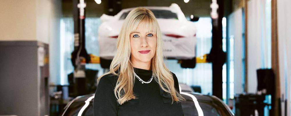 Laura Schwab standing in front of white Aston Martin on lift