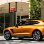 Orange Aston Martin DBX parked outside H&M