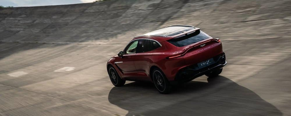 Red Aston Martin DBX driving on outdoor track