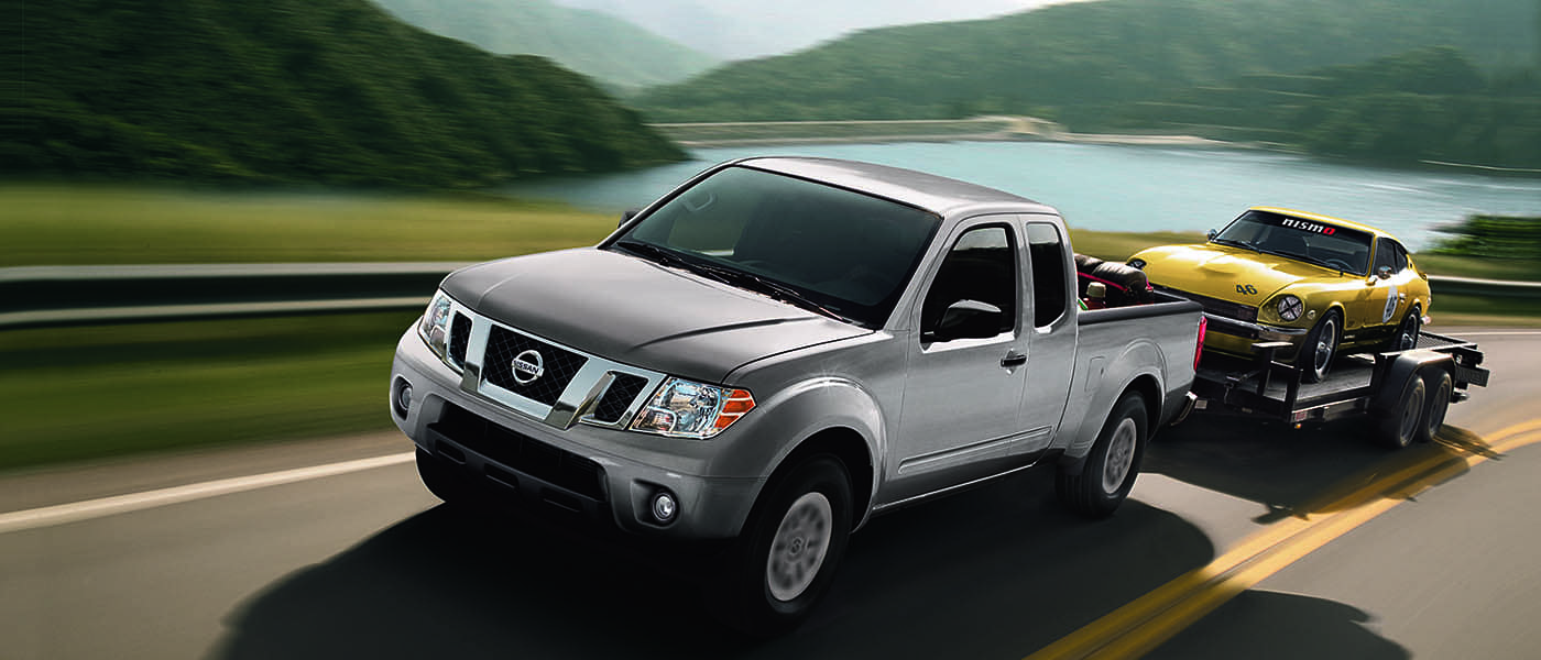2021 Nissan Frontier in grey driving by a river and mountains.