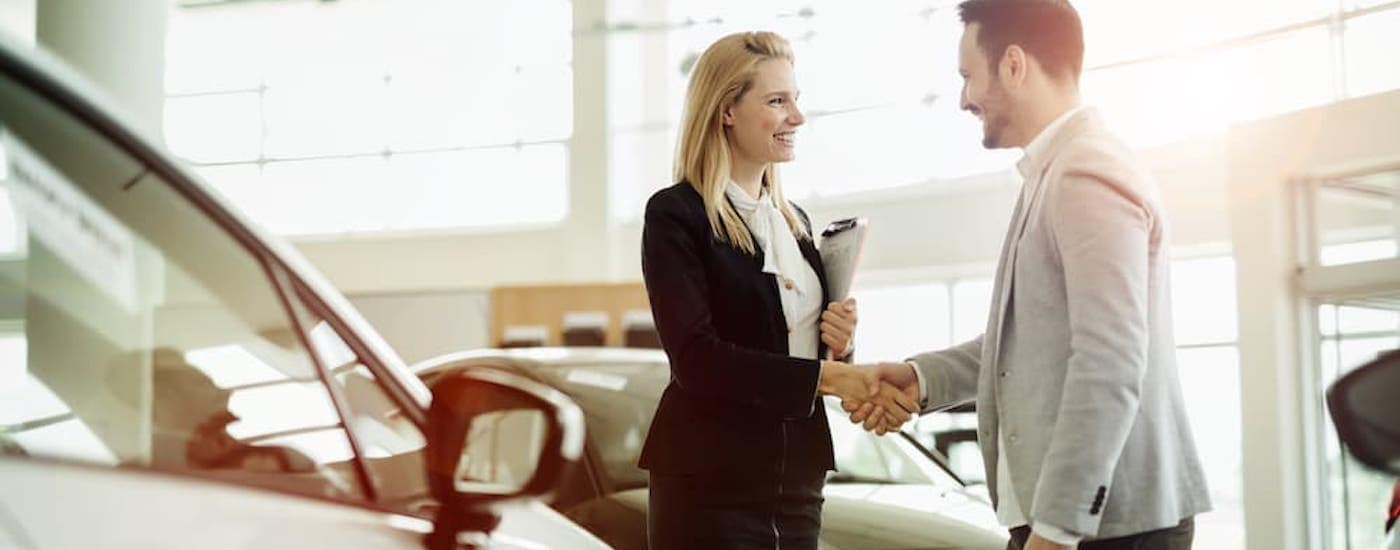 A saleswoman is shaking hands with a customer in the dealership.
