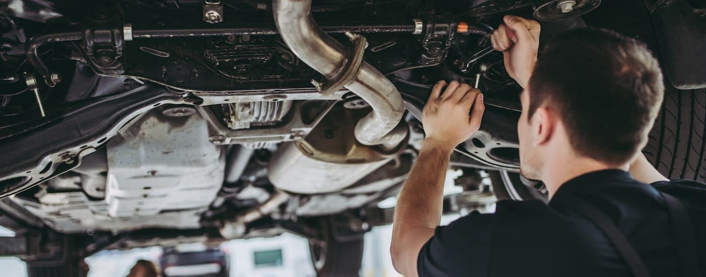 A mechanic is working underneath a car.