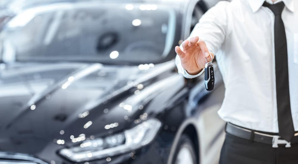 A salesman is holding the key to a black car behind him.