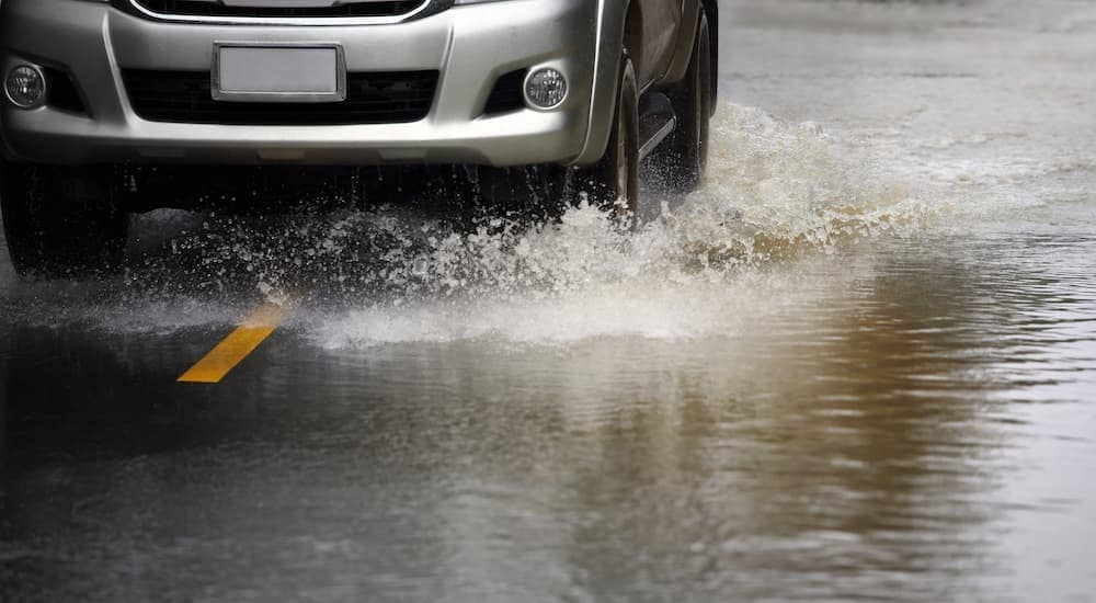 A silver car is driving on a flooded road in Fort Worth, TX.