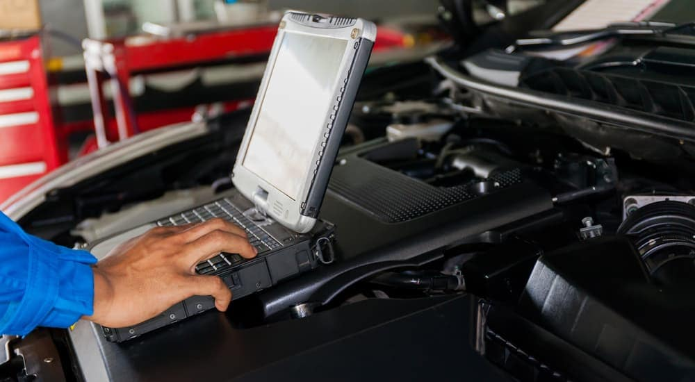 A closeup is shown of a mechanic using a laptop while working on the engine bay of a cheap used car for sale.