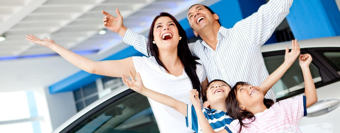 A happy family is shopping for cheap cars near you.