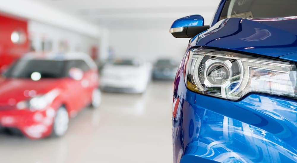 The headlight of a blue car is shown in closeup in a dealership with low priced cars in Fort Worth, TX.