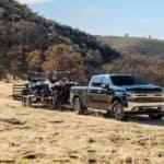 A black 2020 Chevy Silverado Duramax is shown towing two UTVs down a dirt path.