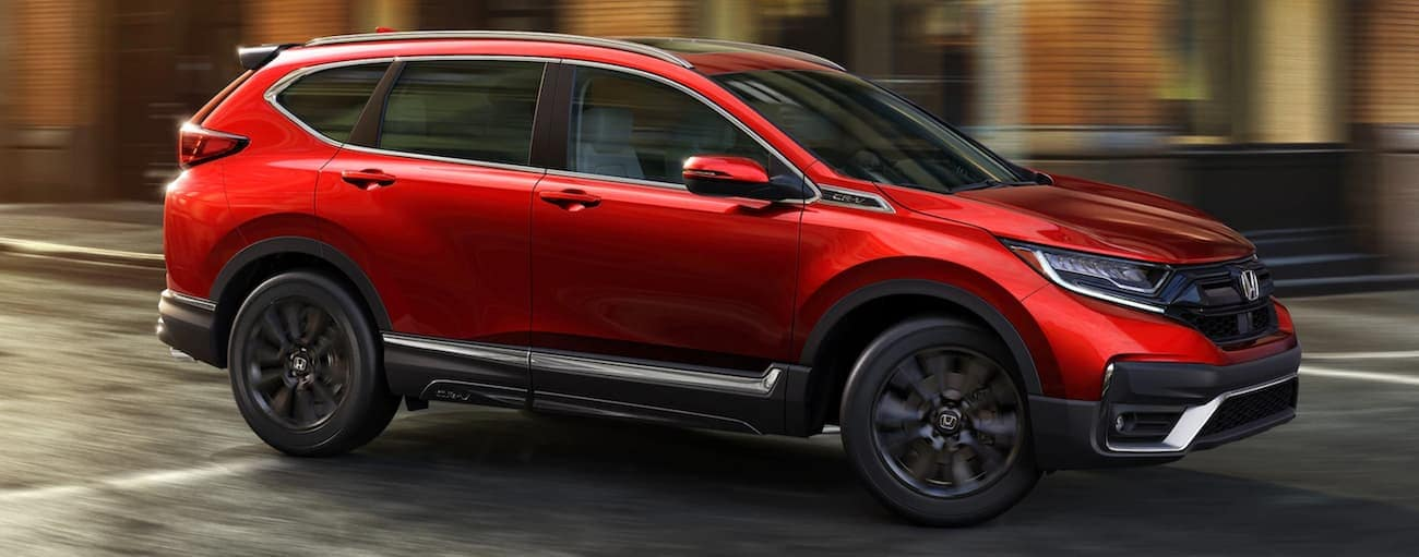 A red 2020 Honda CR-V Touring is driving past blurred buildings near Duluth, GA.