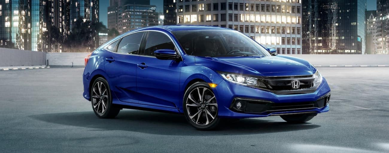 A blue 2020 Honda Civic Sedan Sport is parked in front of city buildings near Duluth, GA, at night.