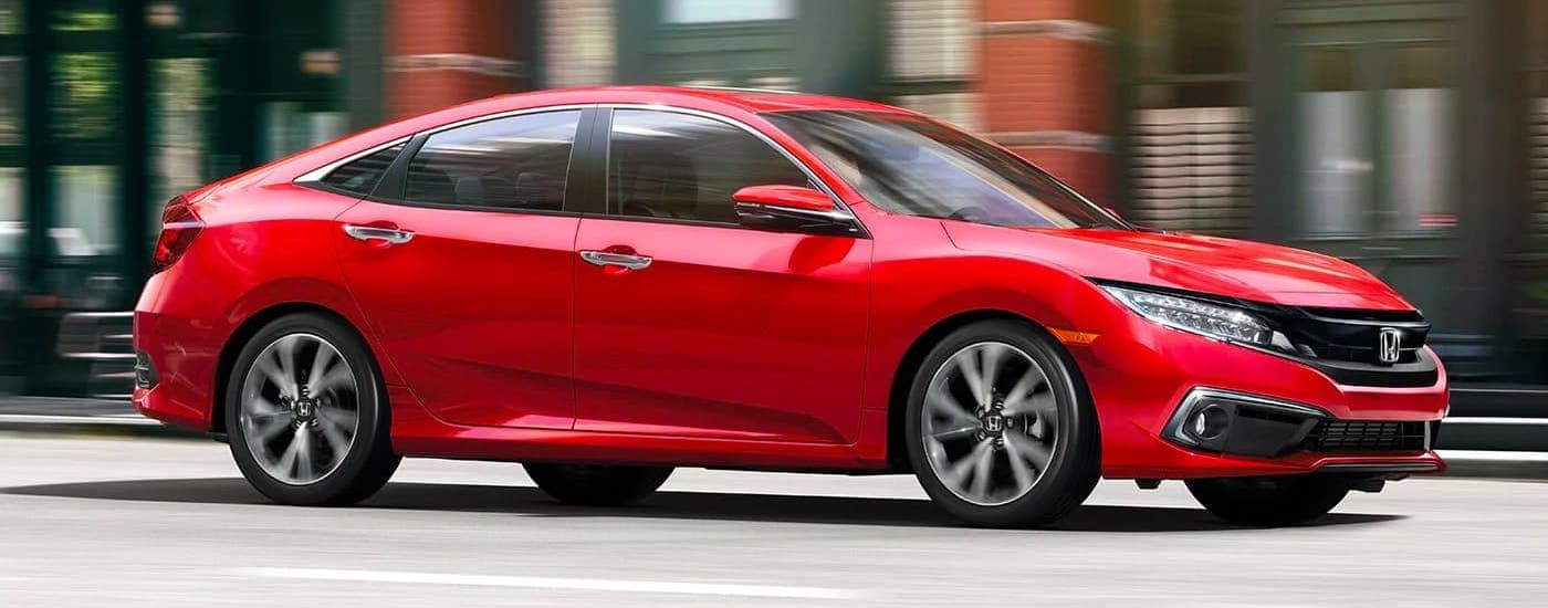 A red 2020 Honda Civic Sedan Touring is driving on a road near Duluth, GA.