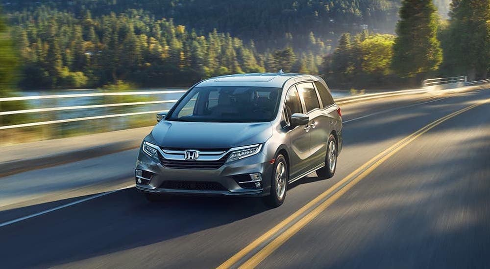 A green 2020 Honda Odyssey Elite is driving on a highway.