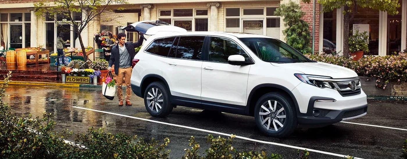 A man is loading groceries into the back of a white 2020 Honda Pilot from a Honda dealer near you.