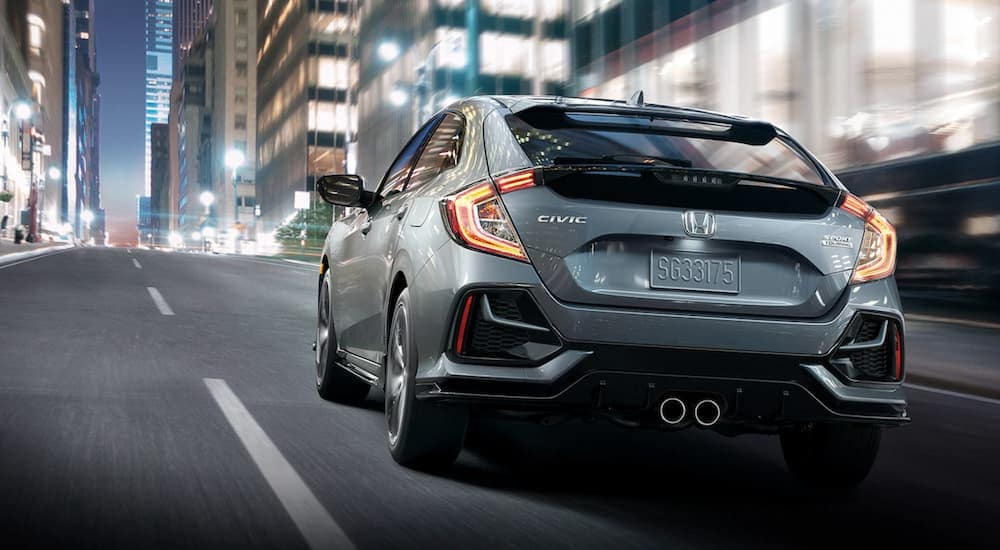 A grey 2020 Honda Civic Hatchback Sport Touring is driving on a city street at night.
