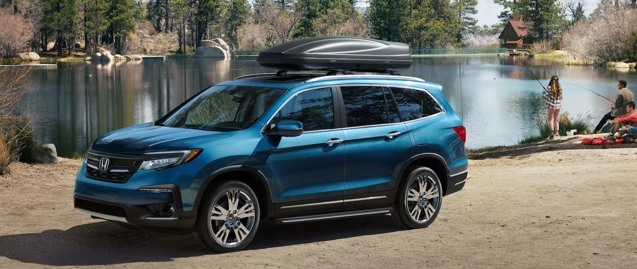 A couple is fishing at a pond next to a blue 2020 Honda Pilot Elite.