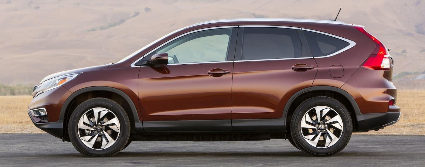 A burgundy 2016 Honda CR-V is shown from the side with a hill in the distance.