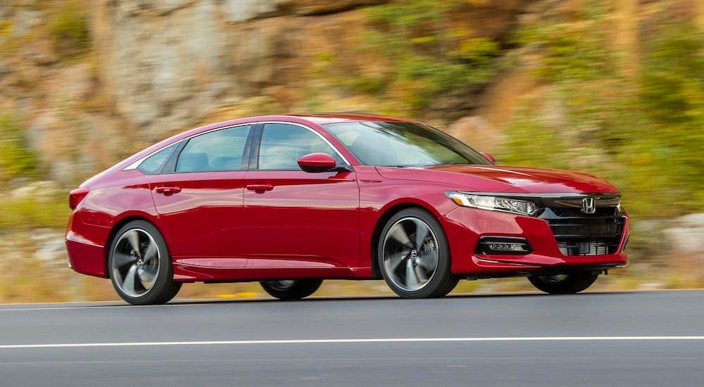 A popular used car near you, a red 2019 Honda Accord, is driving on a highway near Duluth, GA.