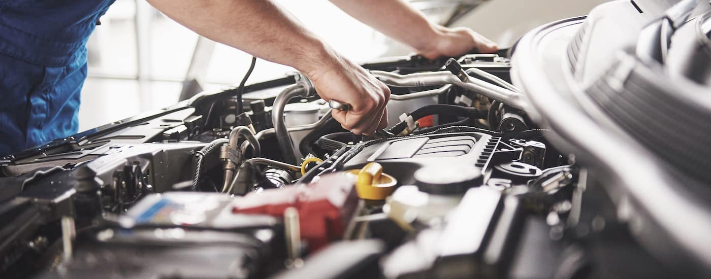A mechanic is working in the engine bay of a vehicle.