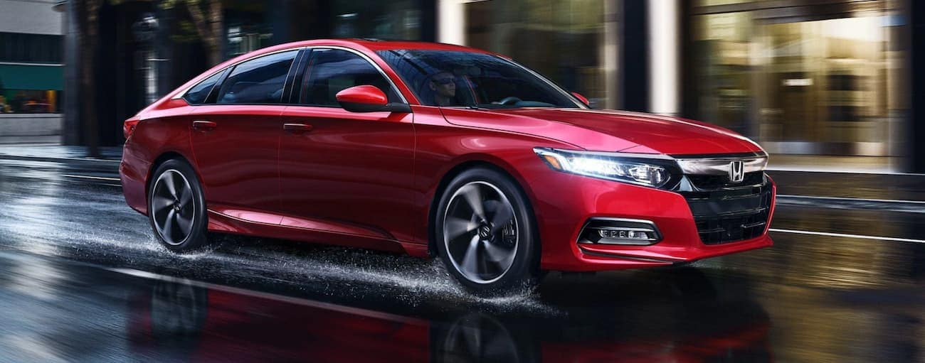 A red 2020 Honda Accord Sport 2.0T is driving on a wet city road near Duluth, GA.