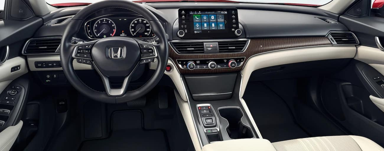 The white and black interior of a 2020 Honda Accord Touring 2.0T is shown of the forward view.
