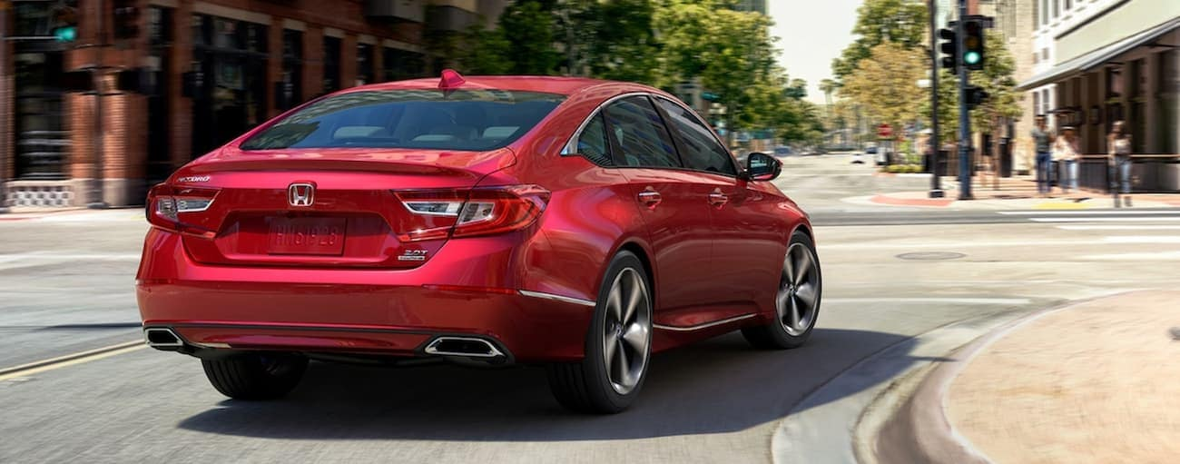 A red 2020 Honda Accord Touring 2.0T is taking a turn on a city road.