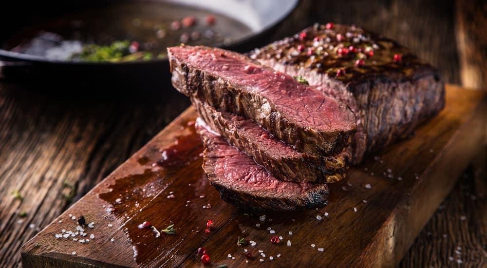 Cut steak is shown on a butcher block.