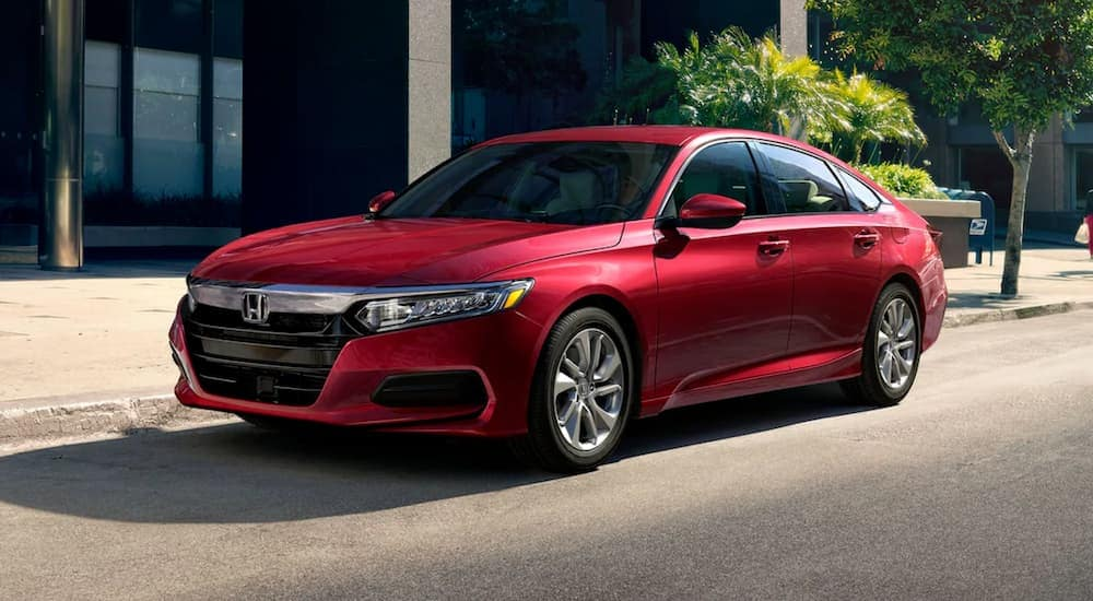 A red 2020 Honda Accord LX is parked on a city street after leaving a Honda dealer near me in Duluth, GA.