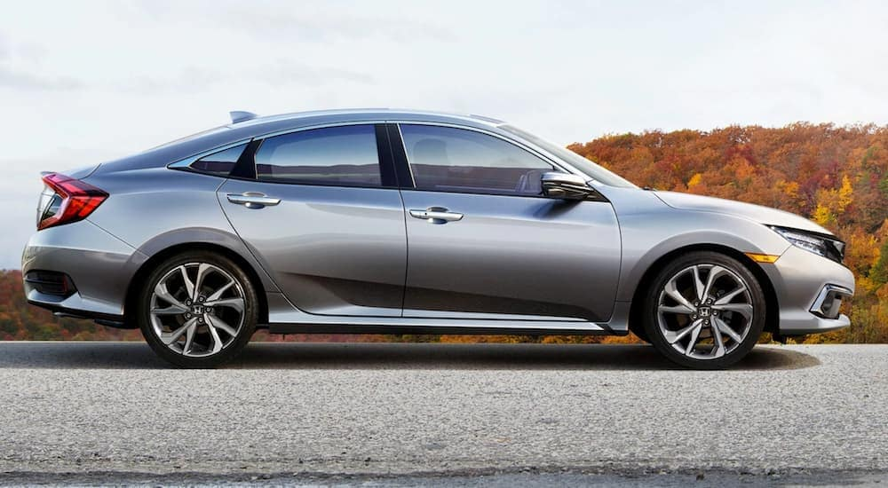 A silver 2020 Honda Civic Touring is shown from the side in front of foliage.