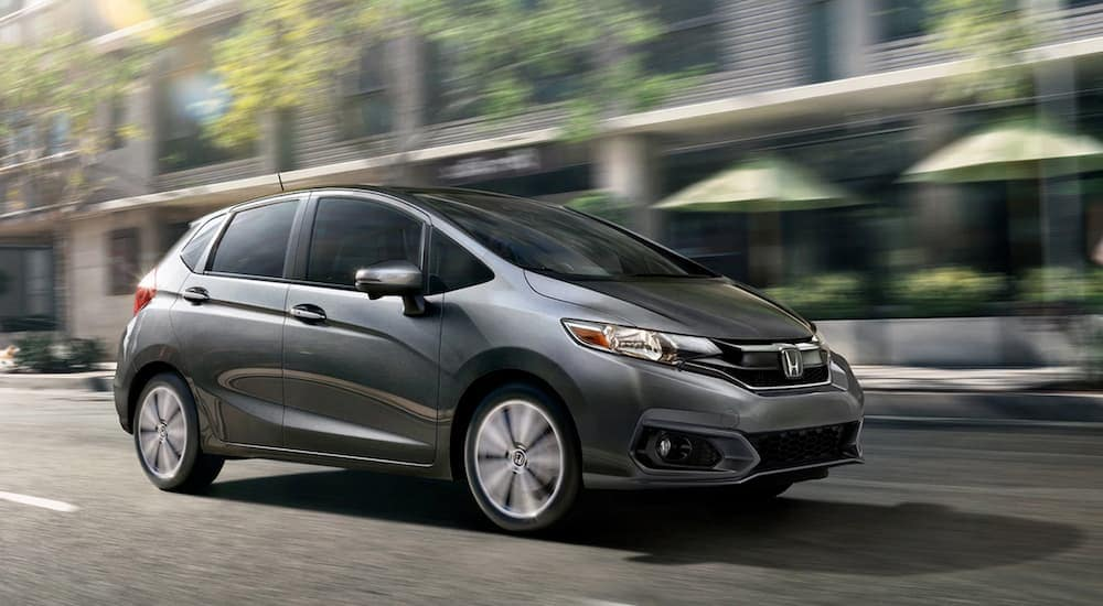 A grey 2020 Honda Fit EX-L, which is popular among Honda models, is driving on a city street near Duluth, GA.