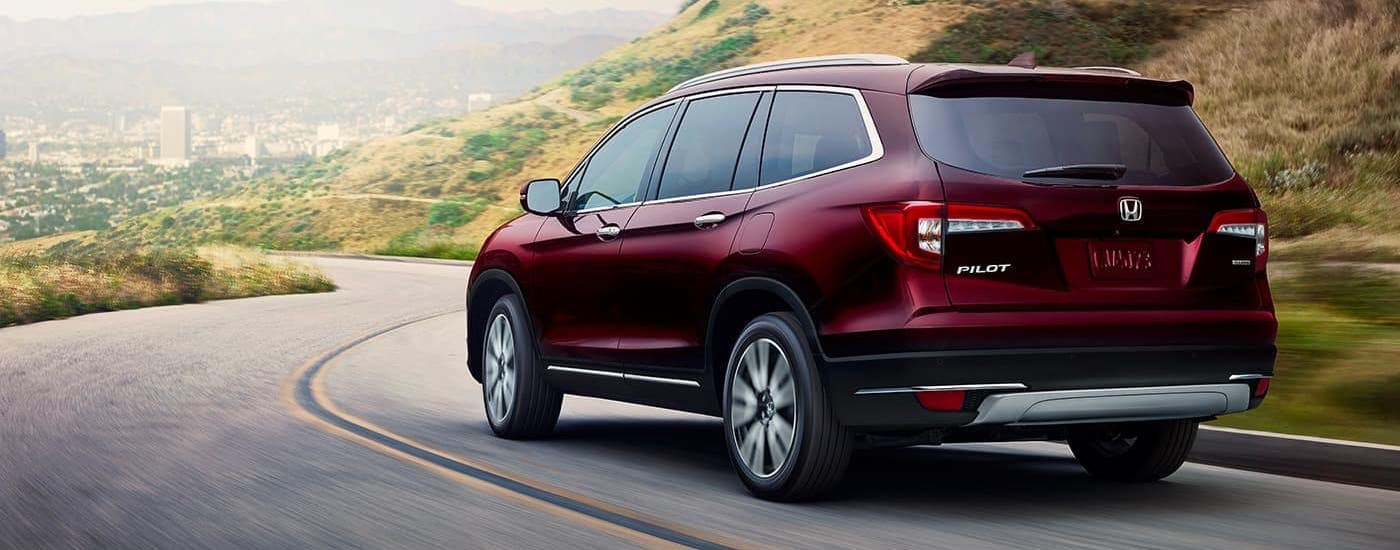 A maroon 2020 Honda Pilot Touring is driving on a hilly highway.