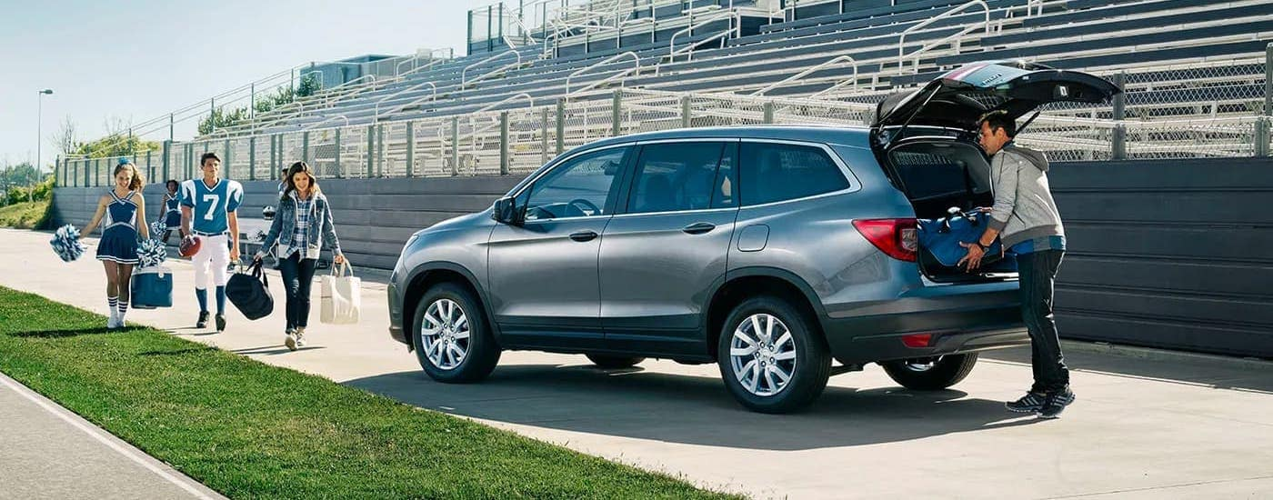 A football family is walking towards a gray 2020 Honda Pilot LX that is parked at a stadium near Duluth, GA.