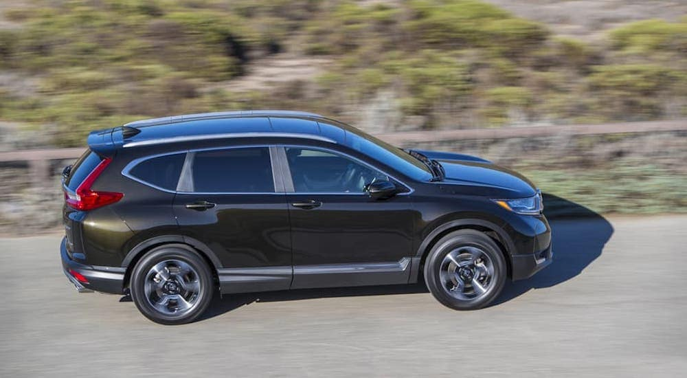 A black 2018 Honda CR-V is driving on an empty road and shown from the side and a high angle.