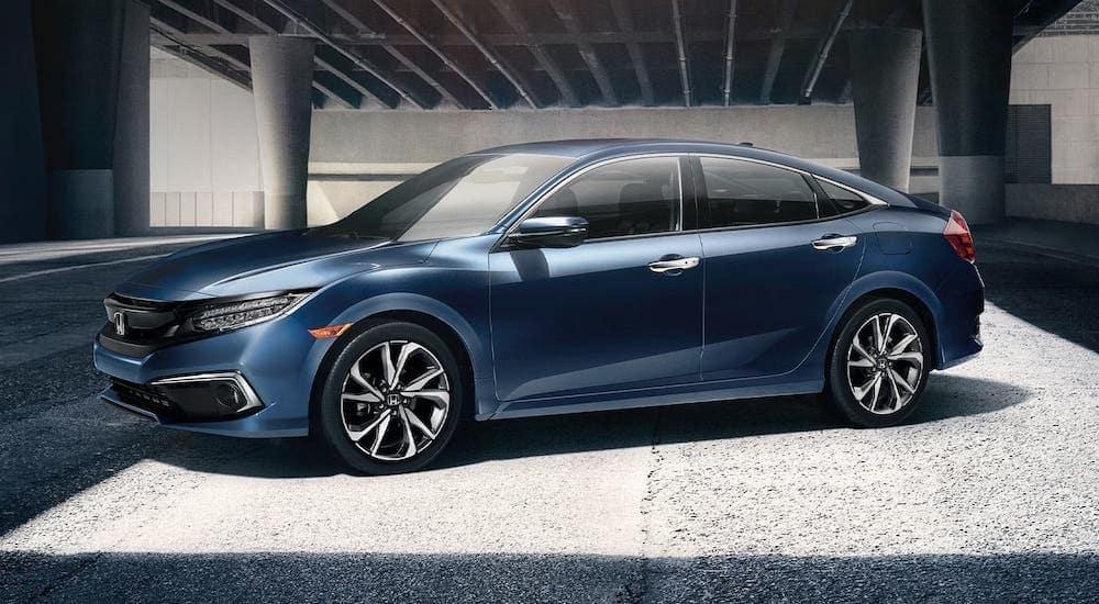 A blue 2020 Honda Civic Touring, a popular model at Honda dealers, is parked under a bridge near Atlanta, GA.