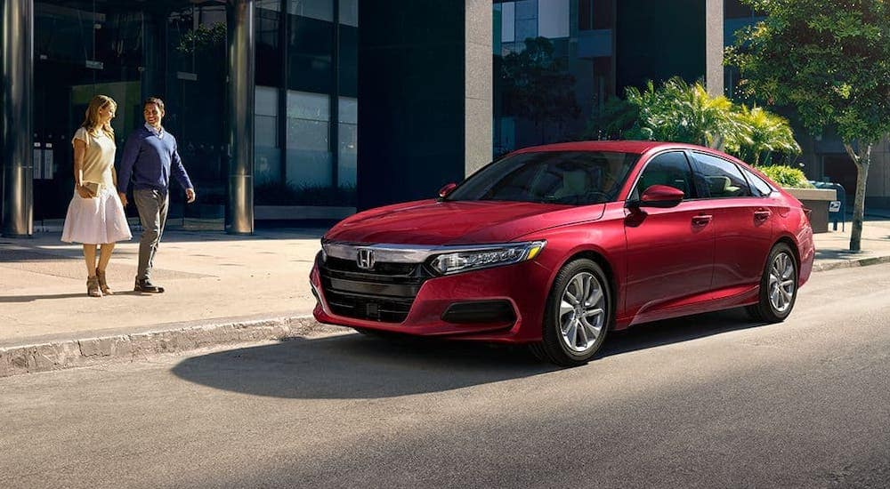 A couple is walking towards a red 2020 Honda Accord LX which is parked on an Atlanta street.