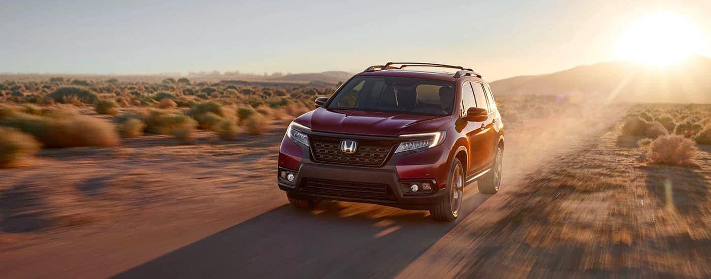 A red 2020 Honda Passport AWD Elite is driving in a desert.