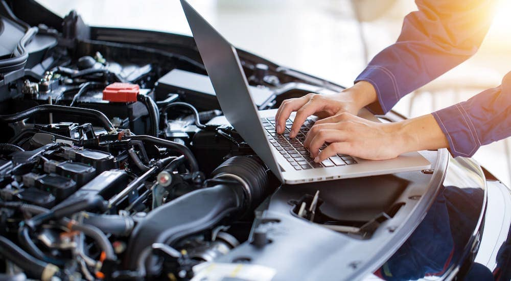 A mechanic is using a laptop on a car's engine bay at a Honda dealer's service center.