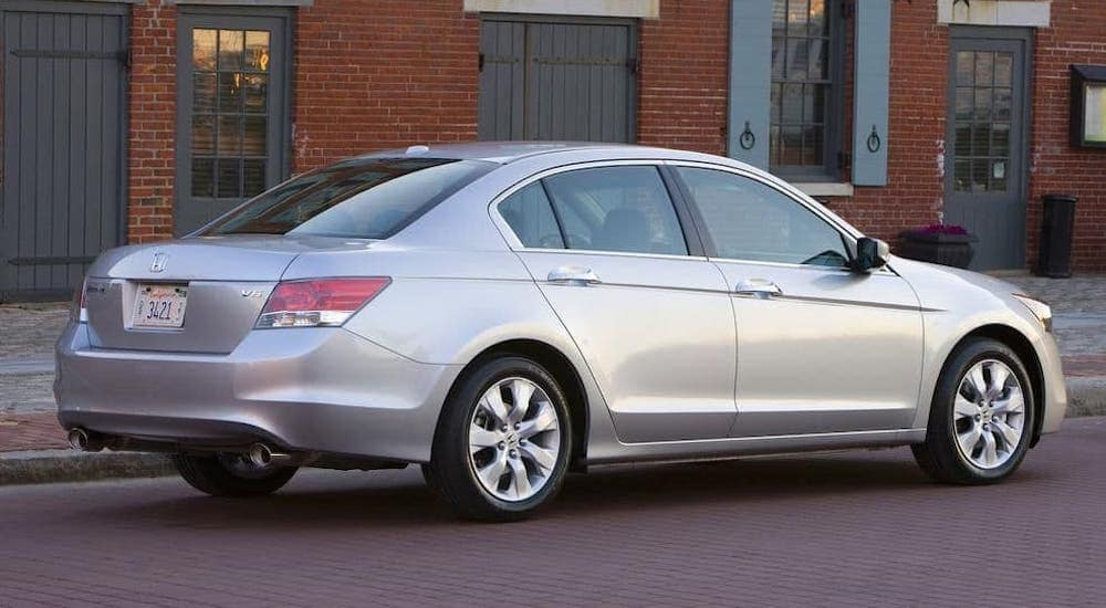 A silver 2009 Honda Accord EX-L V6 is parked in front of a red brick building.
