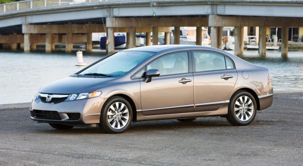 A gray 2011 Honda Civic LX is parked in front of a river at sunset.