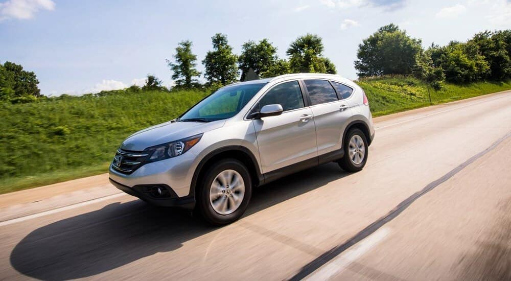 A popular used car for sale in Duluth, GA, a silver 2014 Honda CR-V LX, is shown driving on highway.