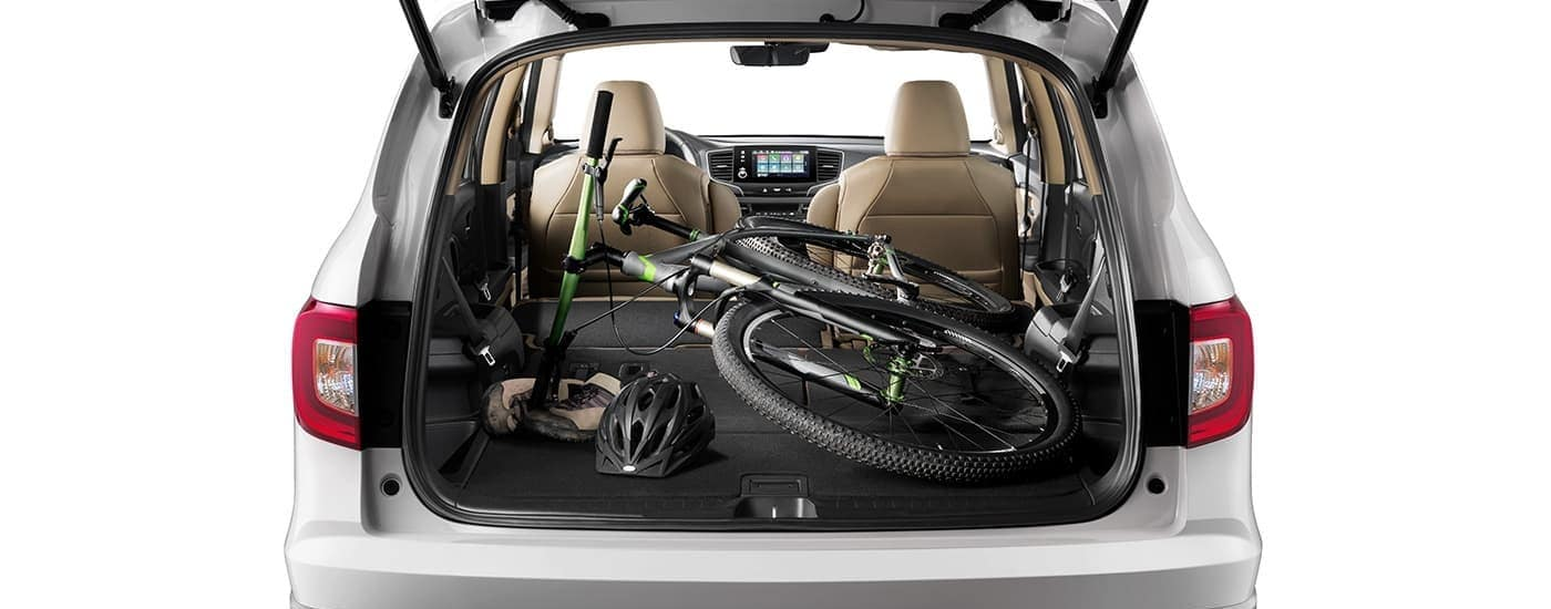 A bicycle and bike gear are shown in the cargo area of a silver 2021 Honda Pilot EX-L.