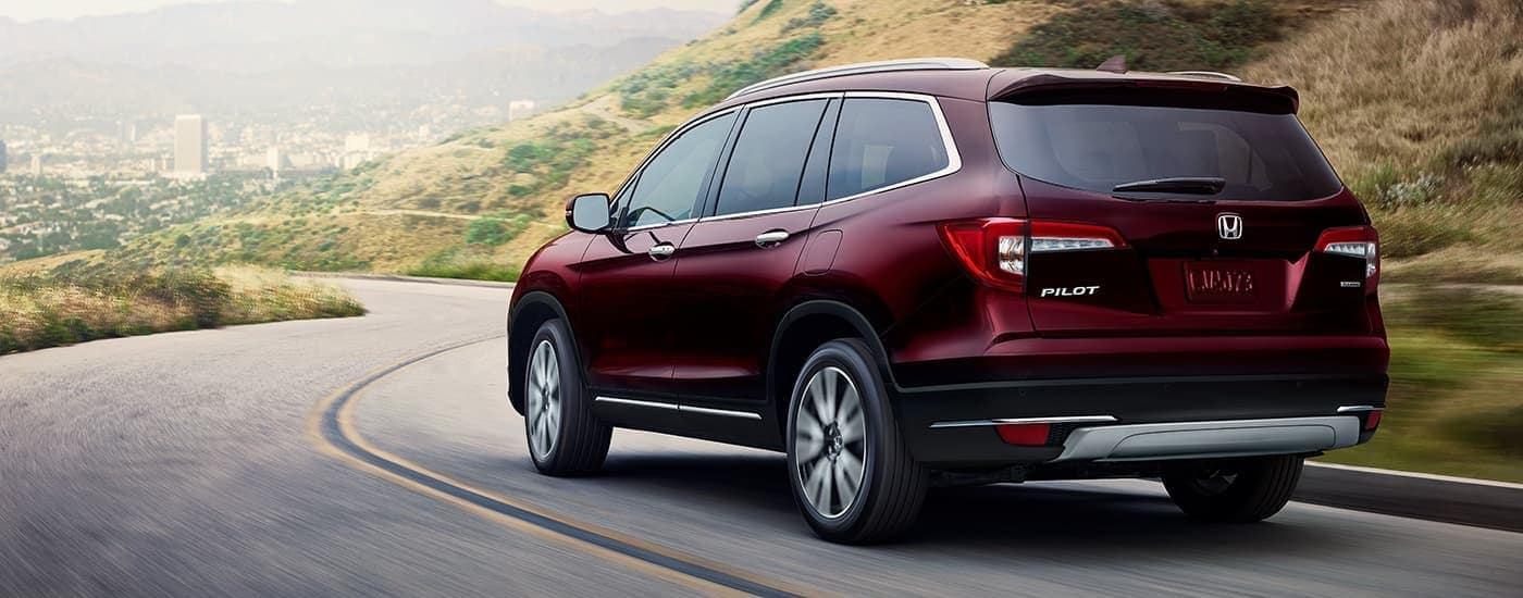 A maroon 2021 Honda Pilot Touring is driving on a highway near Duluth, GA.
