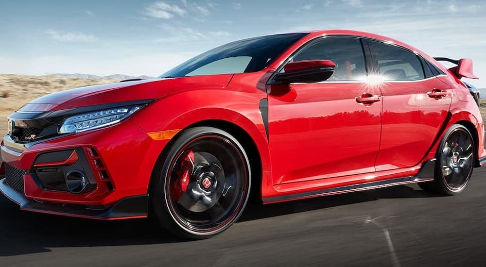 One of the new Hondas for sale in Duluth, GA, a red 2021 Honda Civic Type R is shown driving on a street.
