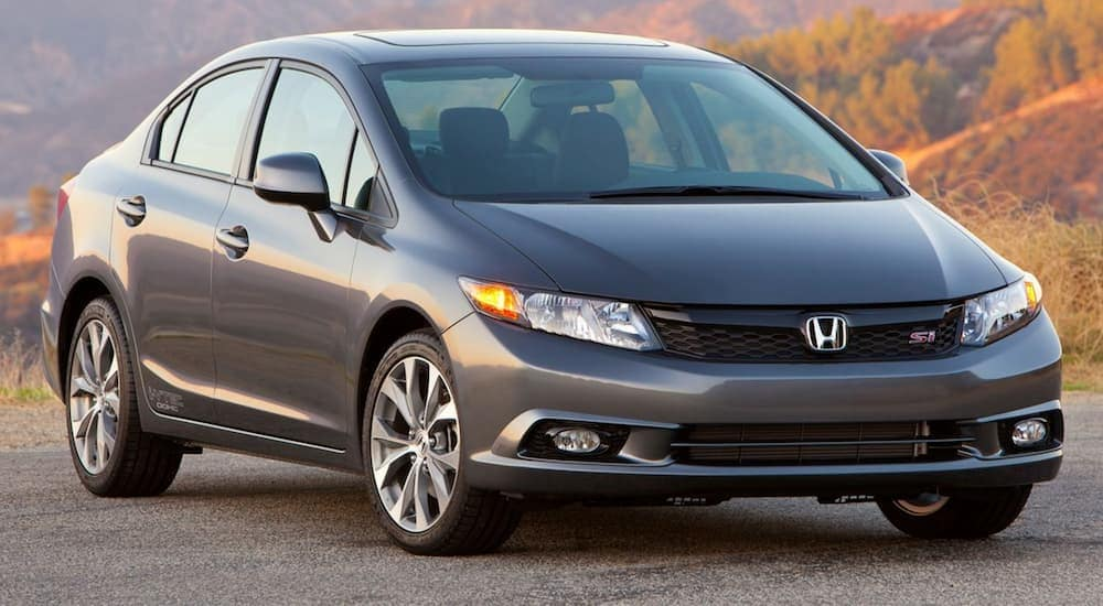 A grey popular used car near me, a 2014 Honda Civic Si, is parked in front of fall foliage.