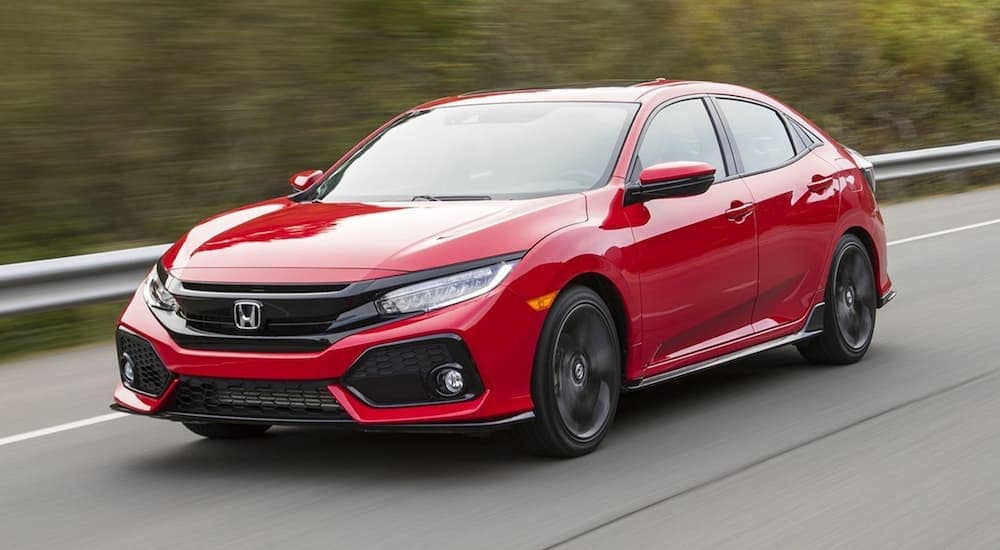 A red 2017 Honda Civic is driving past a blurred guard rail in Duluth, GA.