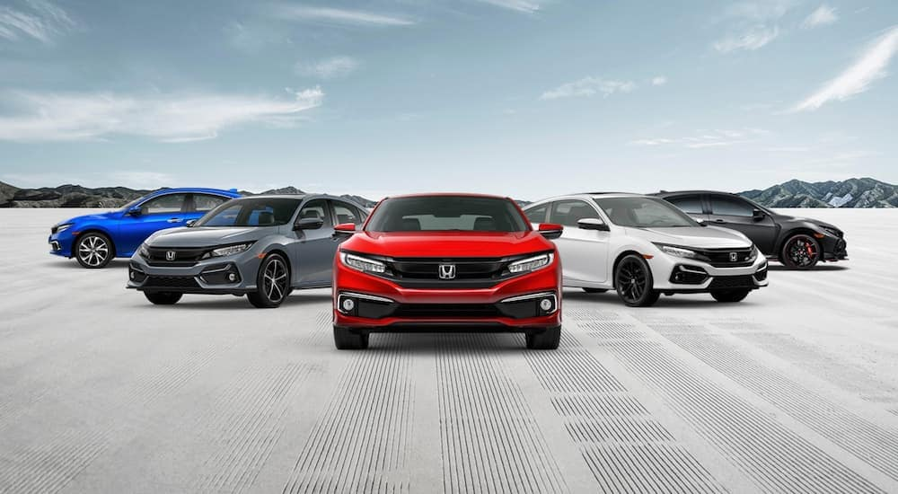 Five different 2020 Honda Civic models are parked in front of distant mountains.