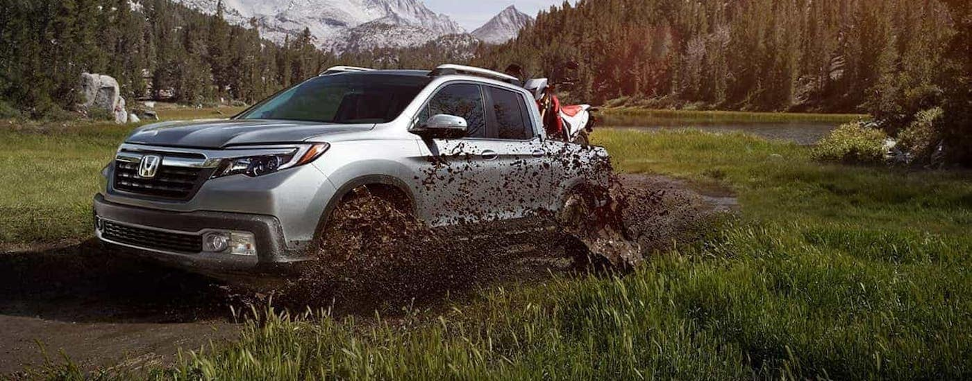 A silver 2020 Honda Ridgeline AWD RTL-E with dirtbike in the bed is shown splashing through mud.