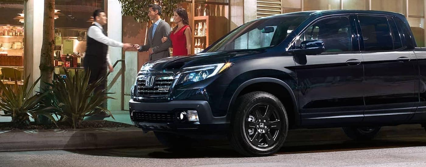 A couple is handing keys to their black 2020 Honda Ridgeline Black Edition to a valet in front of a Duluth restaurant.