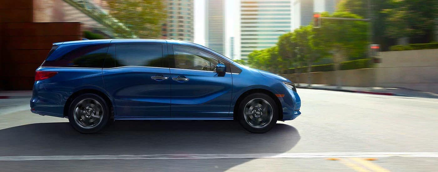 A blue 2021 Honda Odyssey Elite is shown from the side while driving on a city street.