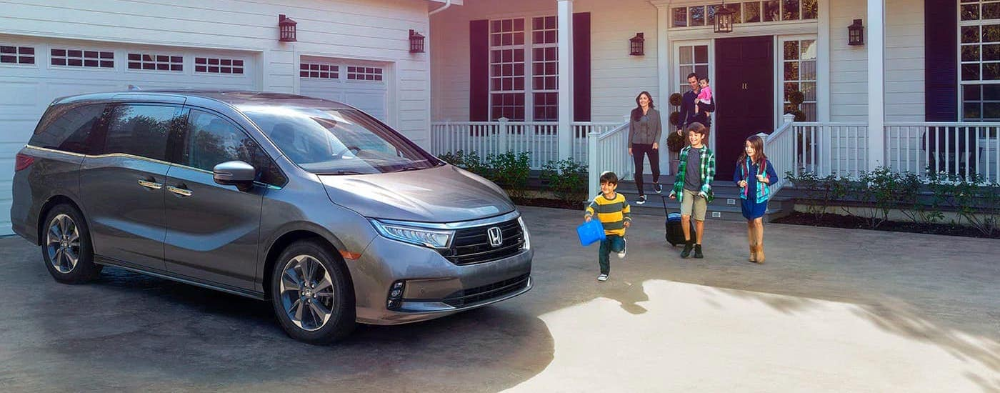 A family is walking towards a gray 2021 Honda Odyssey in front of their Duluth home.