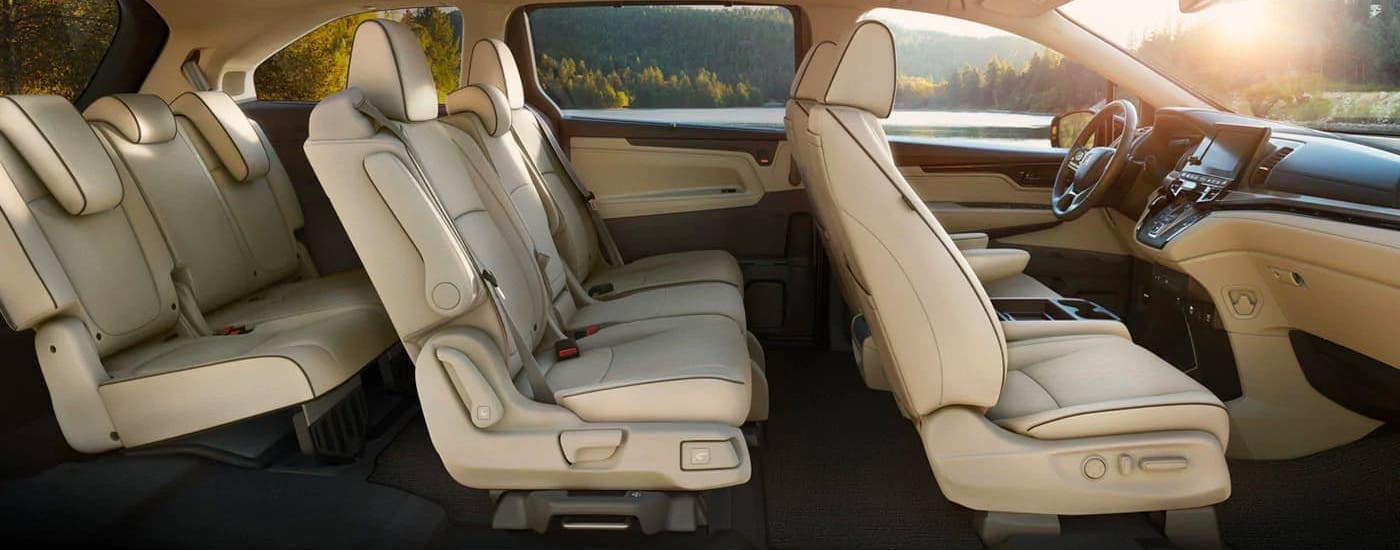 The three rows of cream-colored seats in a 2021 Honda Odyssey Elite are shown from the side.